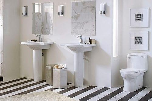 White sinks and toilet on zebra tile floor