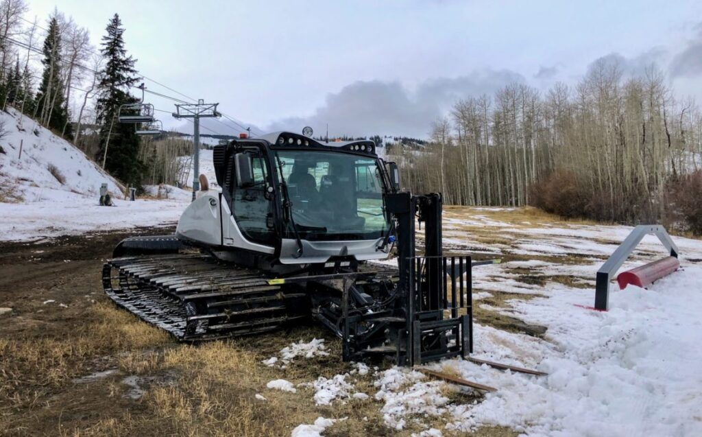 A snowcat sits on grass just days before Snowmass Ski Area opened this winter. As temperatures warm, ski resorts could face shorter seasons, less snowpack and more challenges making artificial snow. This year, it snowed heavily just before SkiCo opened Aspen Mountain and Snowmass the weekend before Thanksgiving. Photo by Elizabeth Stewart-Severy/Aspen Journalism