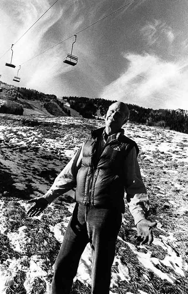 Aspen Ski Corp president D.R.C. Brown stands in front of a nearly bare Little Nell ski run during the dismal ski season of 1976-'77. After this season, SkiCo invested in snowmaking technology to make up for what Mother Nature doesn't always deliver. Photo by Aspen Historical Society, Cassatt Collection