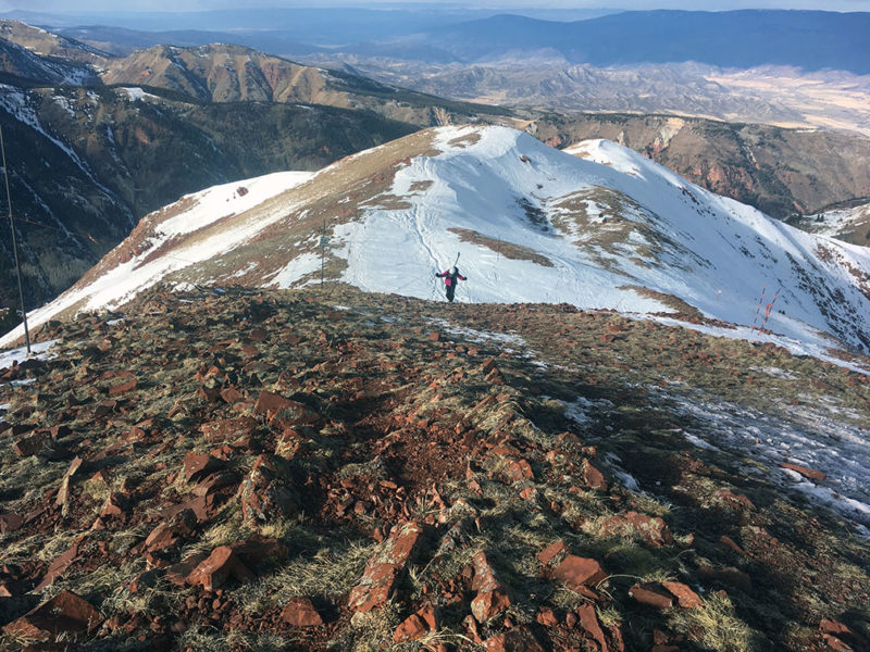 A skier hikes toward the 12,392-foot summit of Aspen Highlands in December 2017, during a low-snow winter. The ridge leading to Highland Bowl is usually covered with snow, even early in the winter. Photo by Catherine Lutz.