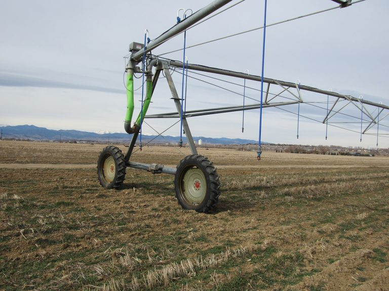 An irrigation system known as a center pivot sprinkler sits in a field near Longmont, Colo. The systems have helped Colorado use its farm water more efficiently, but state use still exceeds the national average. Credit: Jerd Smith
