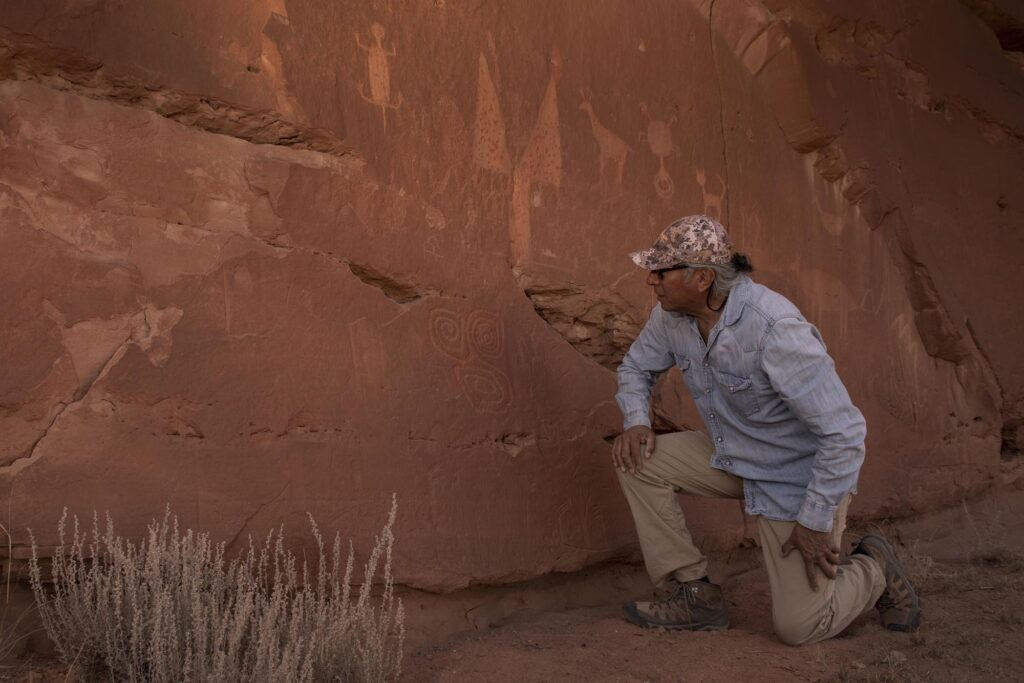 Jim Enote studies petroglyphs on a sandstone cliff in northwest New Mexico produced by a culture that vanished after a likely half-century drought.