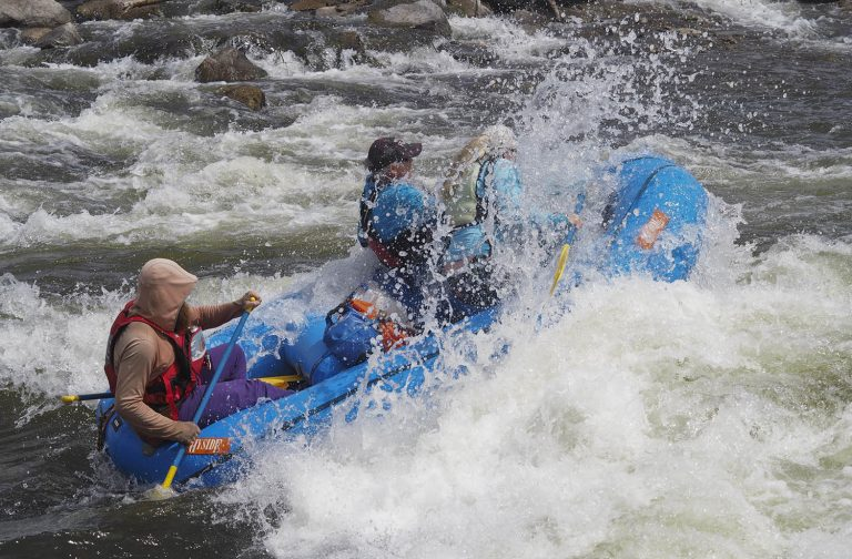 Rafting outfitters in Colorado face the double threat of early snowmelt and travel restrictions from a pandemic.  Rafters and surfers enjoy riding a wave on the Gunnison River near Gunnison, Colo., on May 17, 2020. Credit: Dean Krakel/Special to Fresh Water News