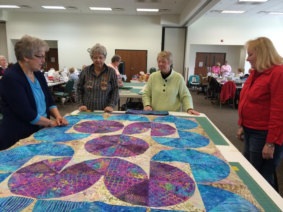 Four quilters study a work in progress