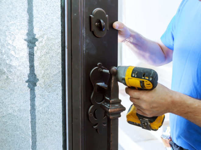 Male handyman carpenter at interior metal door lock installation using screwdriver,