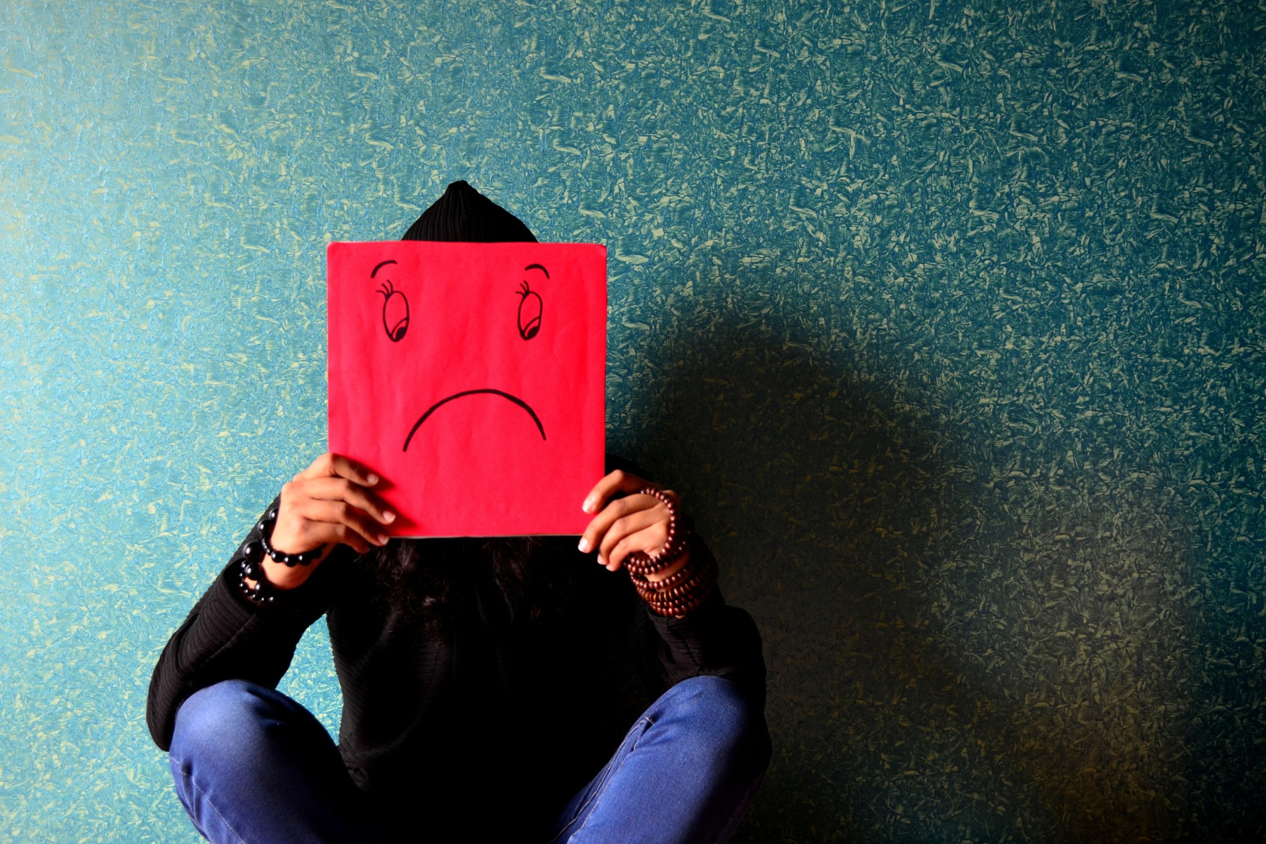 person sitting down holding a sad face
