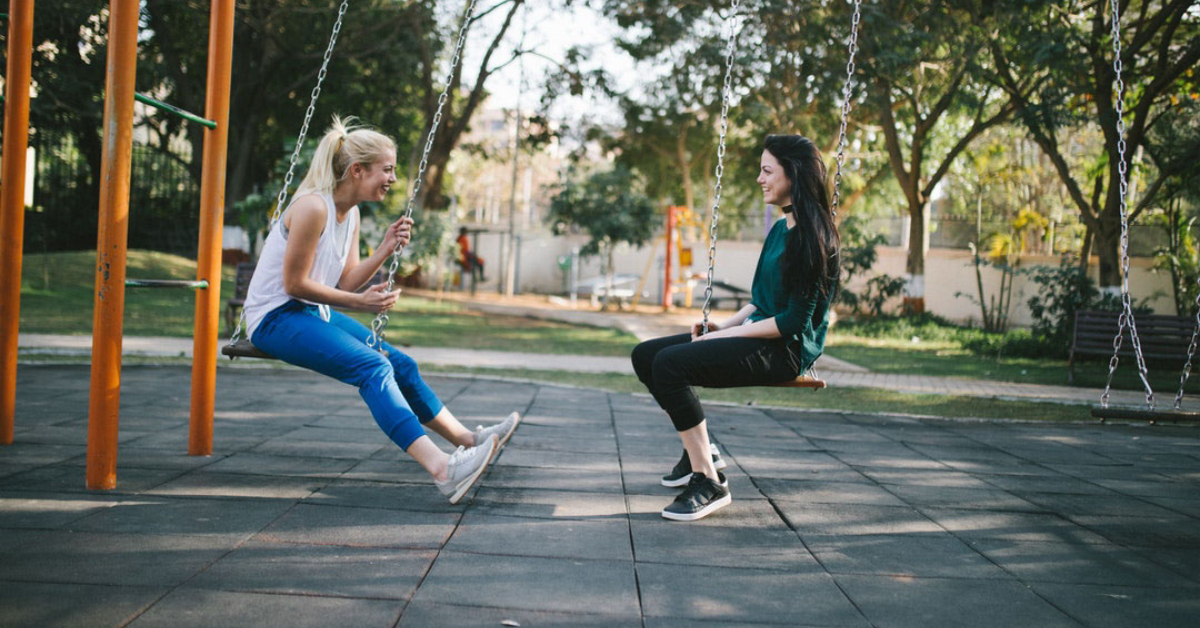 two young women sit on swing set and talk while laughing