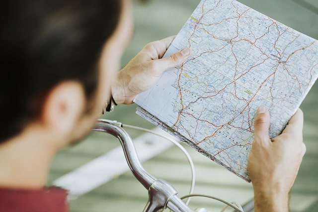 man looking at routes on a map