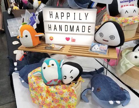 happily handmade sign with plush onigiri and penguins