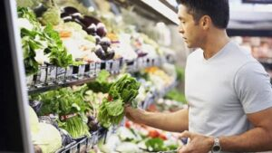 man in supermarket choosing healthy vegetables, liver and COVID research studies