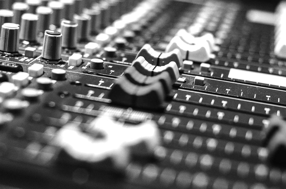 Audio Mixing Board Fader Shot Black and White with buttons and knobs audio production technical angle shot