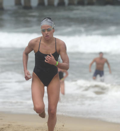 07-31-2011--(Staff Photo by Sean Hiller)-- Taylor Spivey of Redondo Beach is the first woman across the finish line in the annual Dwight Crun Pier-To-Pier Swim Sunday as she finishes at the Manhattan Beach Pier after a rough water swim from the Hermosa Beach Pier.