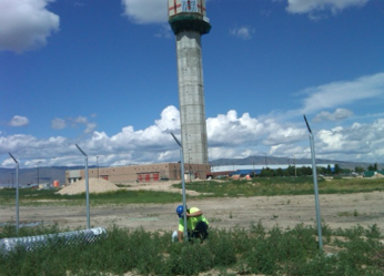 Man working of Fence while Boise Airport tower is in background.