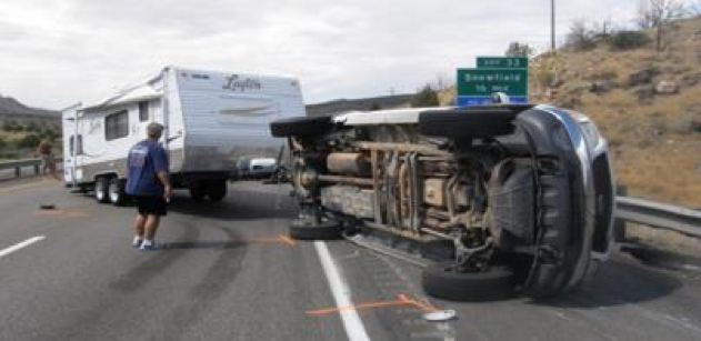 A truck with a trailer. The trailer is obstructing the highway. The truck is on it's side.