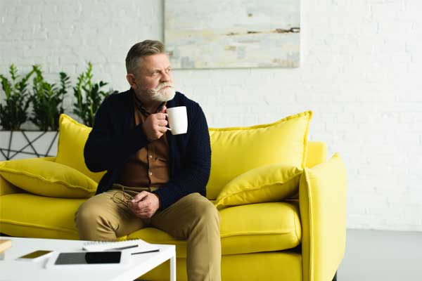 Long-Term Living Homes - Man drinking coffee on sofa