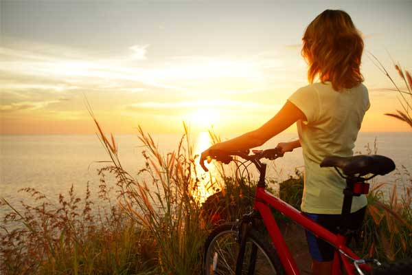 Behavioral Health Living - Woman with bike watching sunset