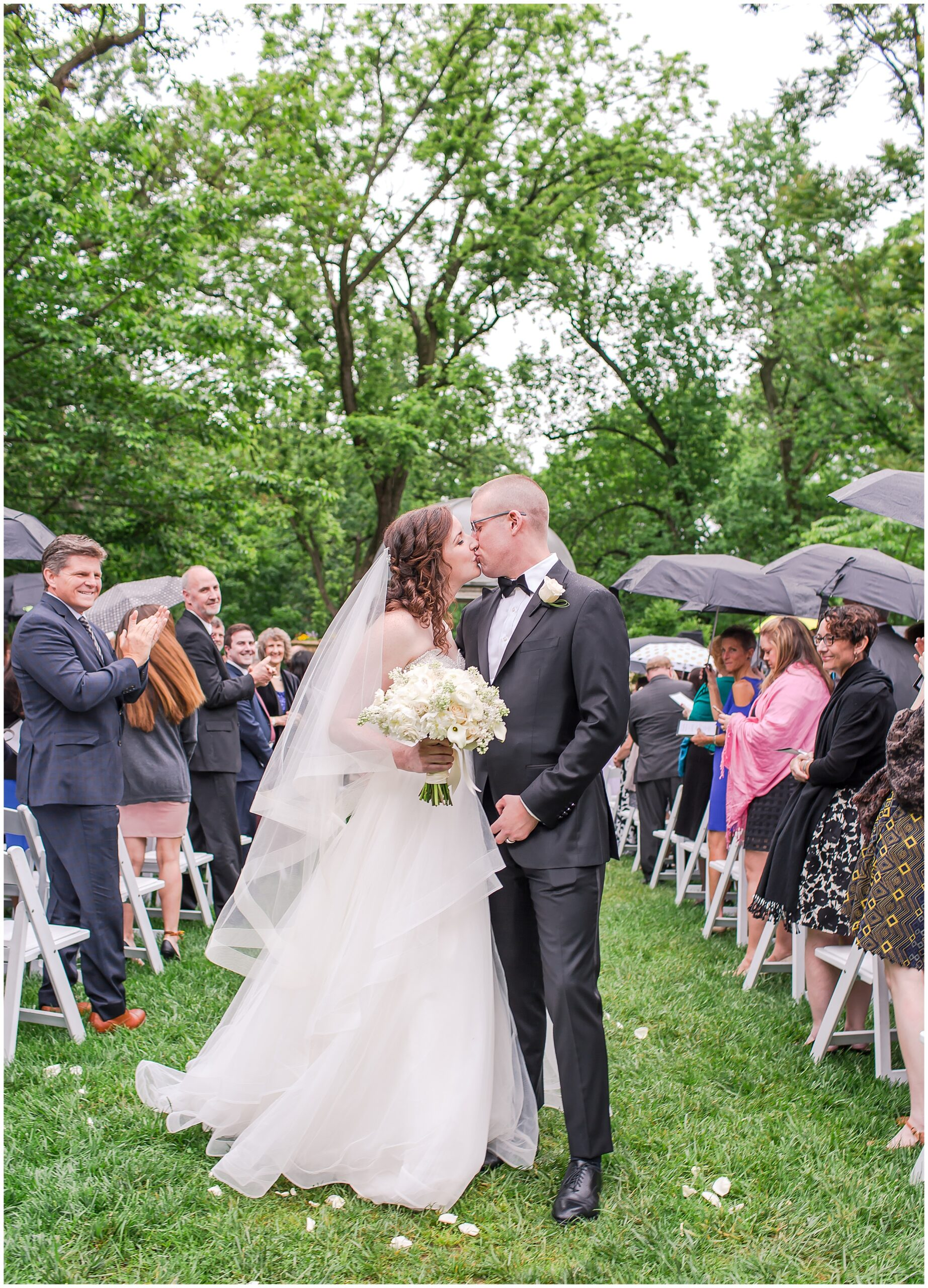 Springtime Omni Shoreham Wedding rain-wedding-outside-just-married-kiss