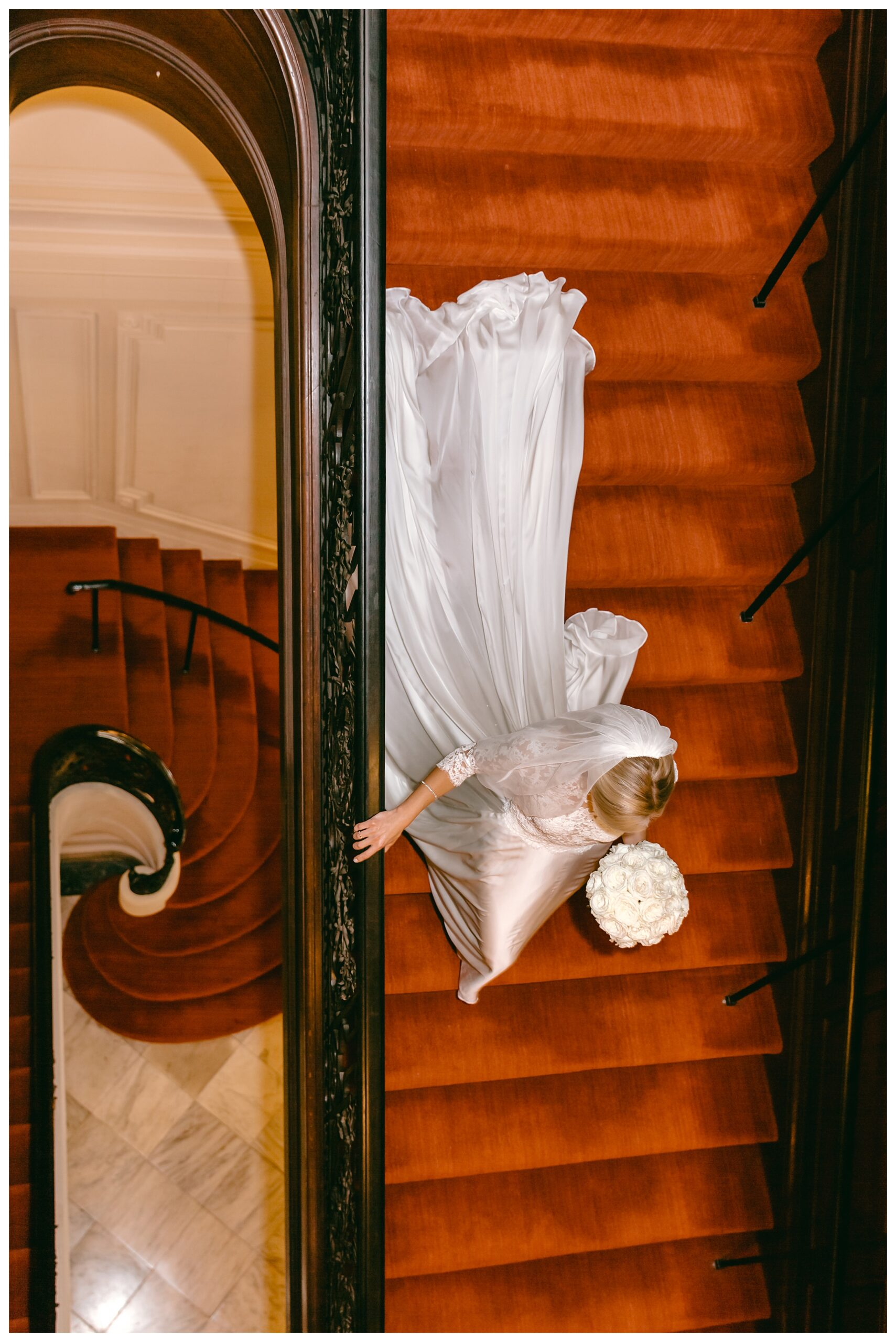 bride from above walking down red carpet of winding stairs