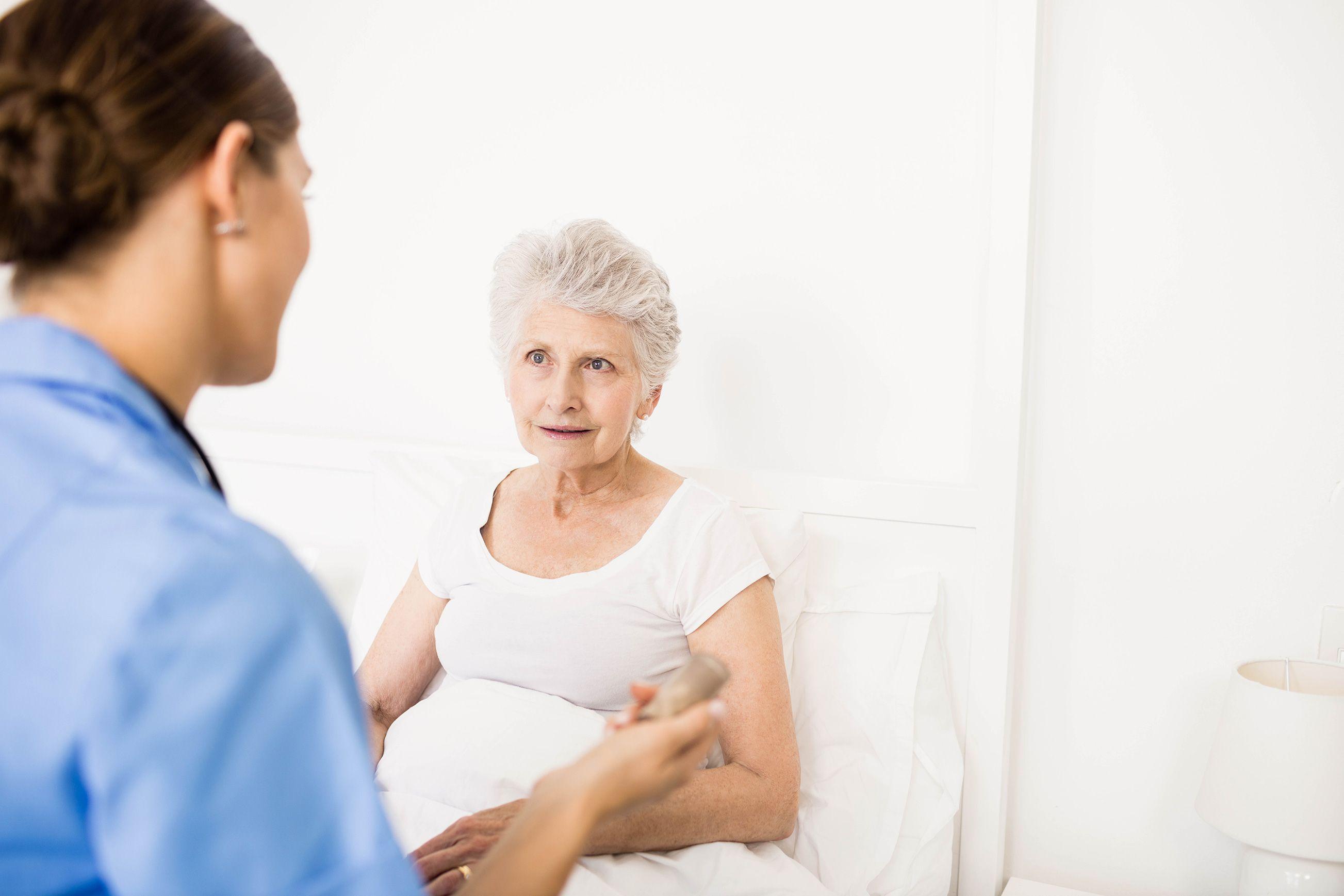 Nurse taking care of elderly woman in a nursing home