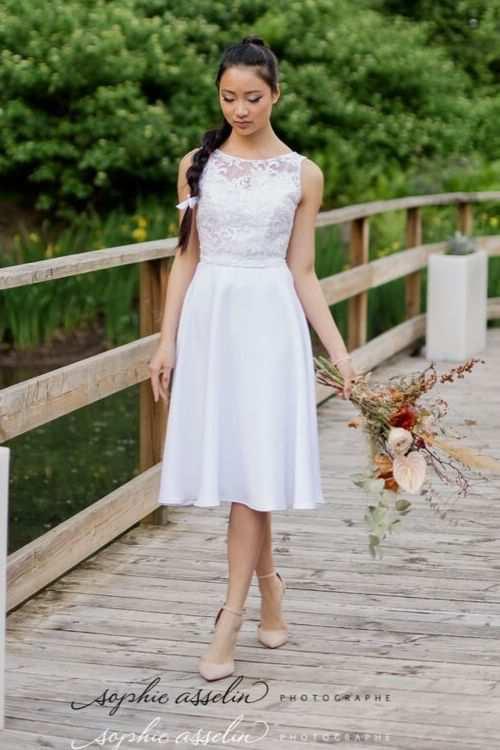 Robe de mariée courte en crêpe de satin et tulle brodé sur le petit pont du parc jean drapeau.