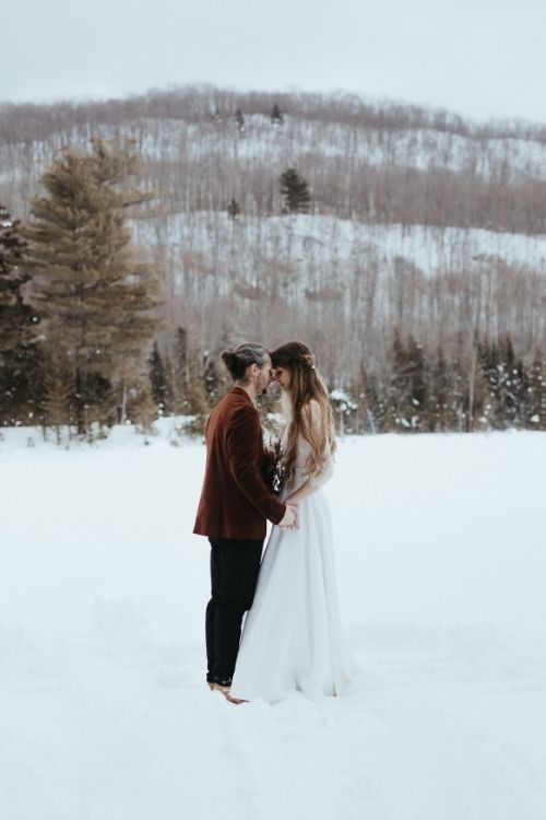 couple se tient au milieu d'un etang gelé