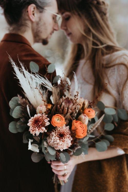 mariés s'enlacant en hiver avec bouquet