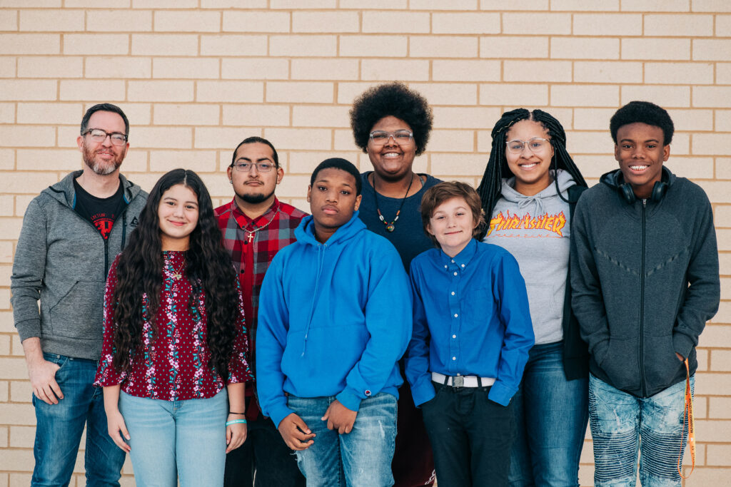 Milestone Democratic School design team, seven youth and one adult standing in front of a brick wall.