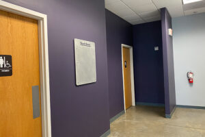 Purple walls with bathroom doors and fire extinguisher mounted on wall.