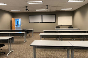 Classroom with rows of tables and two white boards on front wall, two projectors hang from the ceiling.