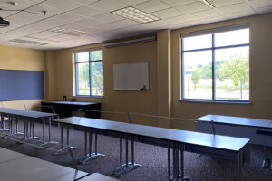 Classroom with windows to green space and front drive, whiteboard on the wall and long tables for a computer lab.