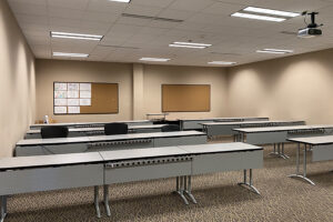 Classroom with long tables that seat three, in rows with cork boards on the back wall.