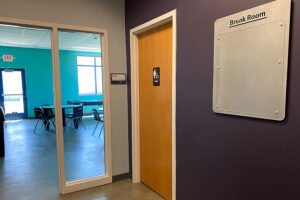 Hallway with restrooms and entry door to student lounge.