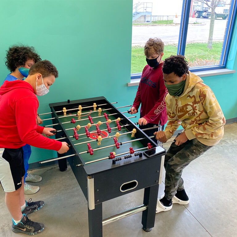 Four students playing foosball in the recreation room.