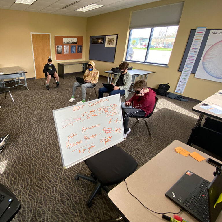 A circle of students in a class with some attending virtually.