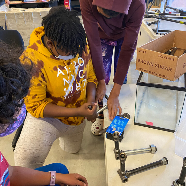 Three students working to assemble parts of an aquaponics tank.