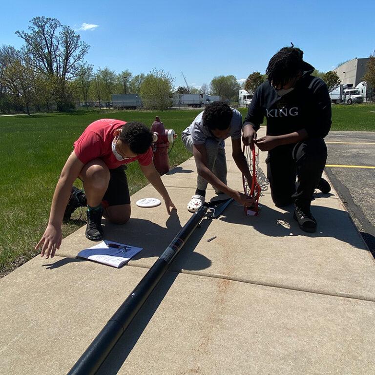 Three students outside assembling a basketball hoop.