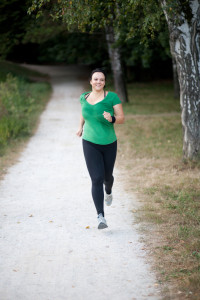 Woman in green tee running trail