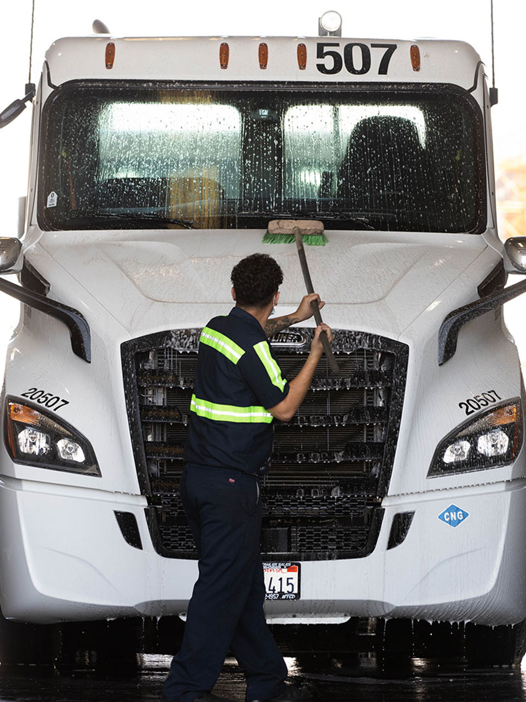 Technician cleaning front hood of Semi cab