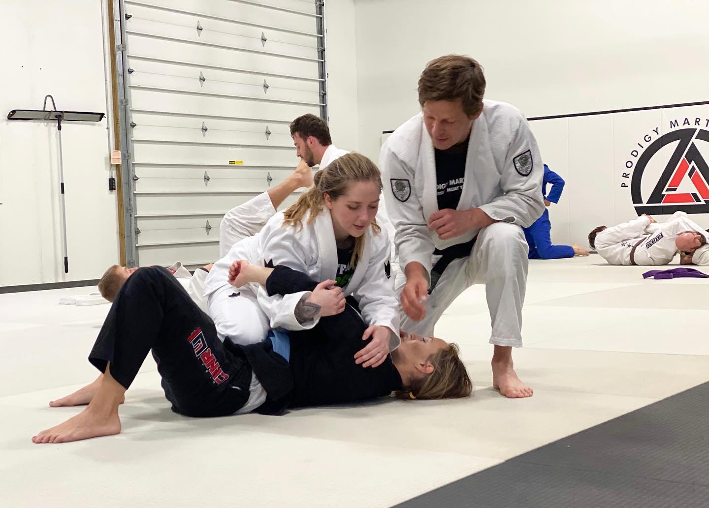 Picture showing two girls doing jiu-jitsu in blaine MN with a jiu-jitsu blackbelt