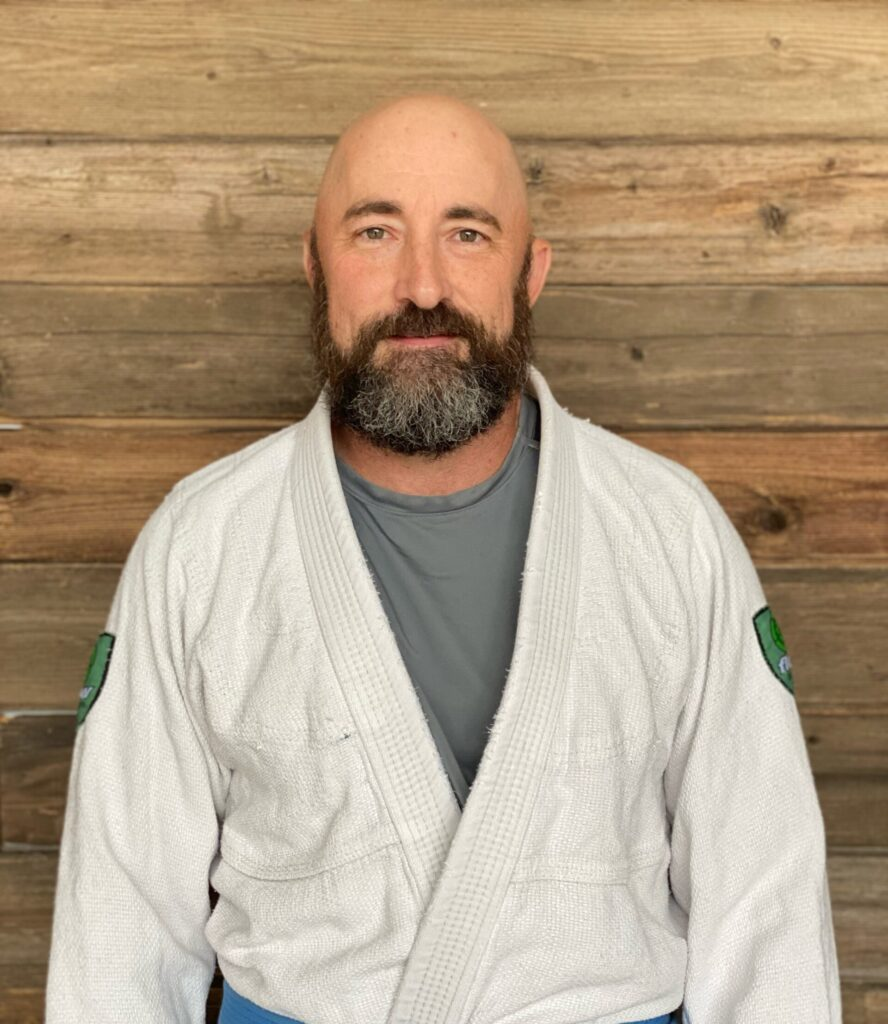 Coach Dave, A Blue Belt In Jiu-Jitsu posing for a picture at Prodigy Martial Arts In Blaine MN With A Wood Background