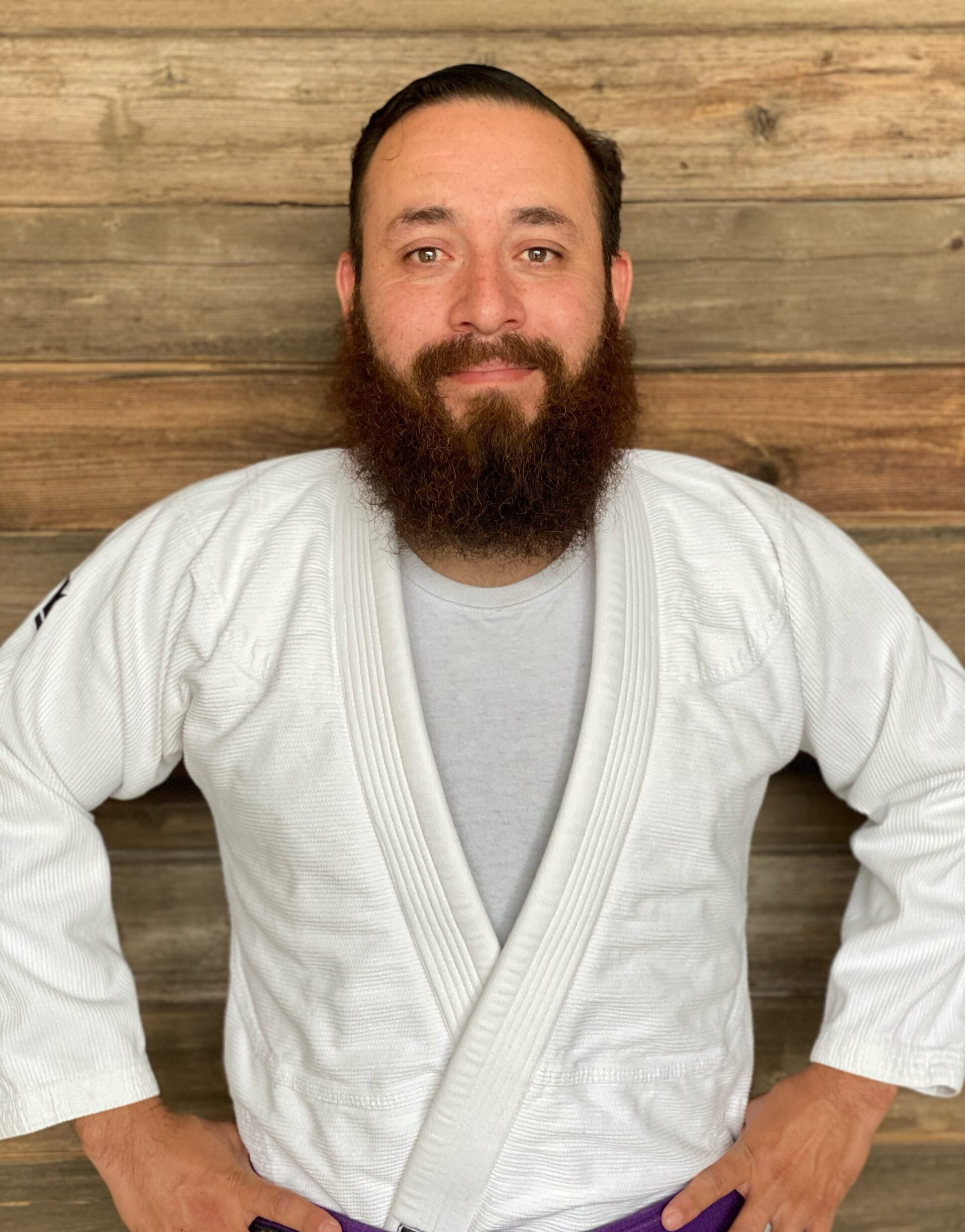 Coach Sal posing for a picture in a white Jiu-Jitsu gi with his black belt on in Blaine MN