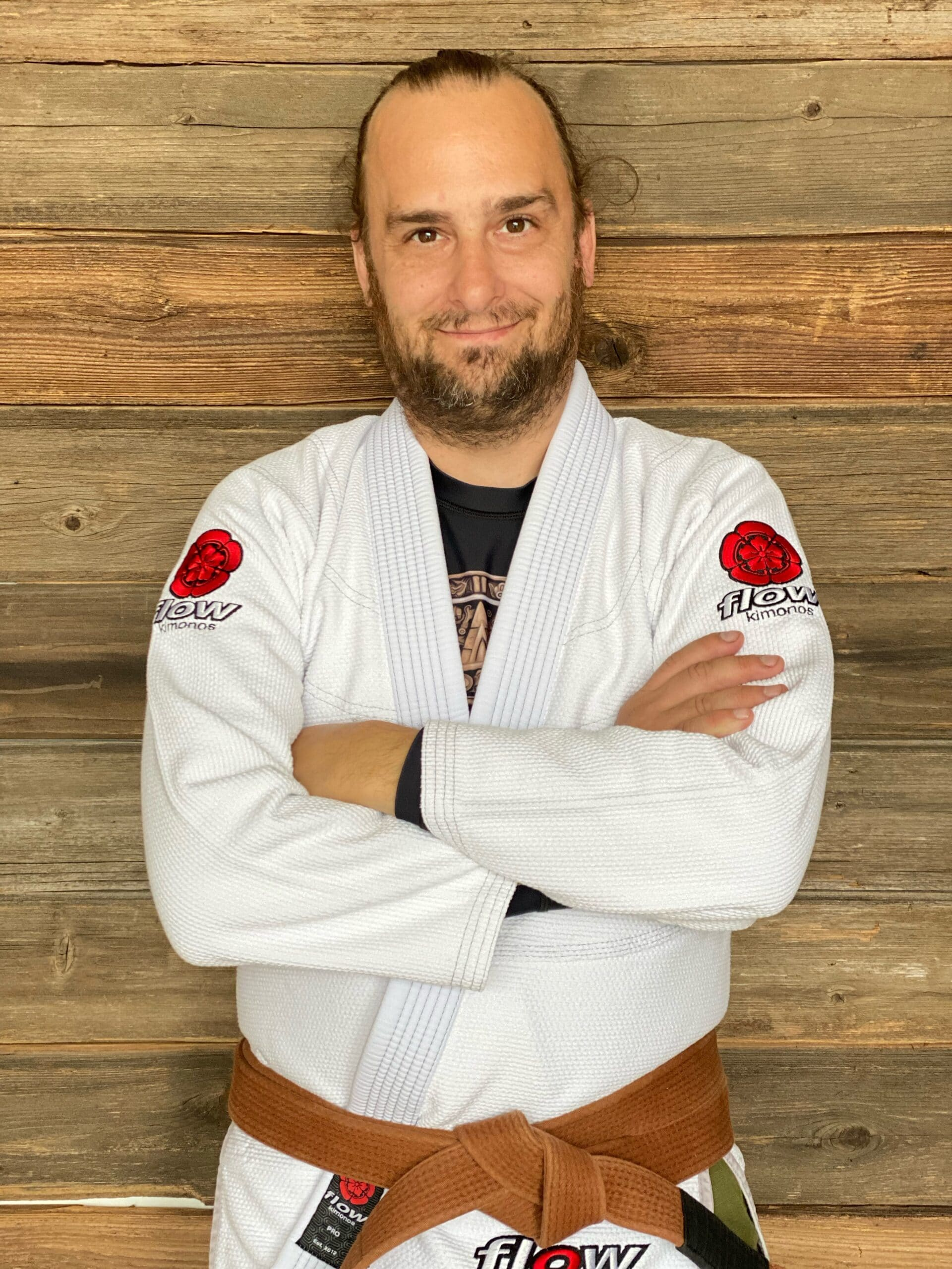 Coach Shane posing for a picture in a white Jiu-Jitsu gi with his brown belt on in Blaine MN