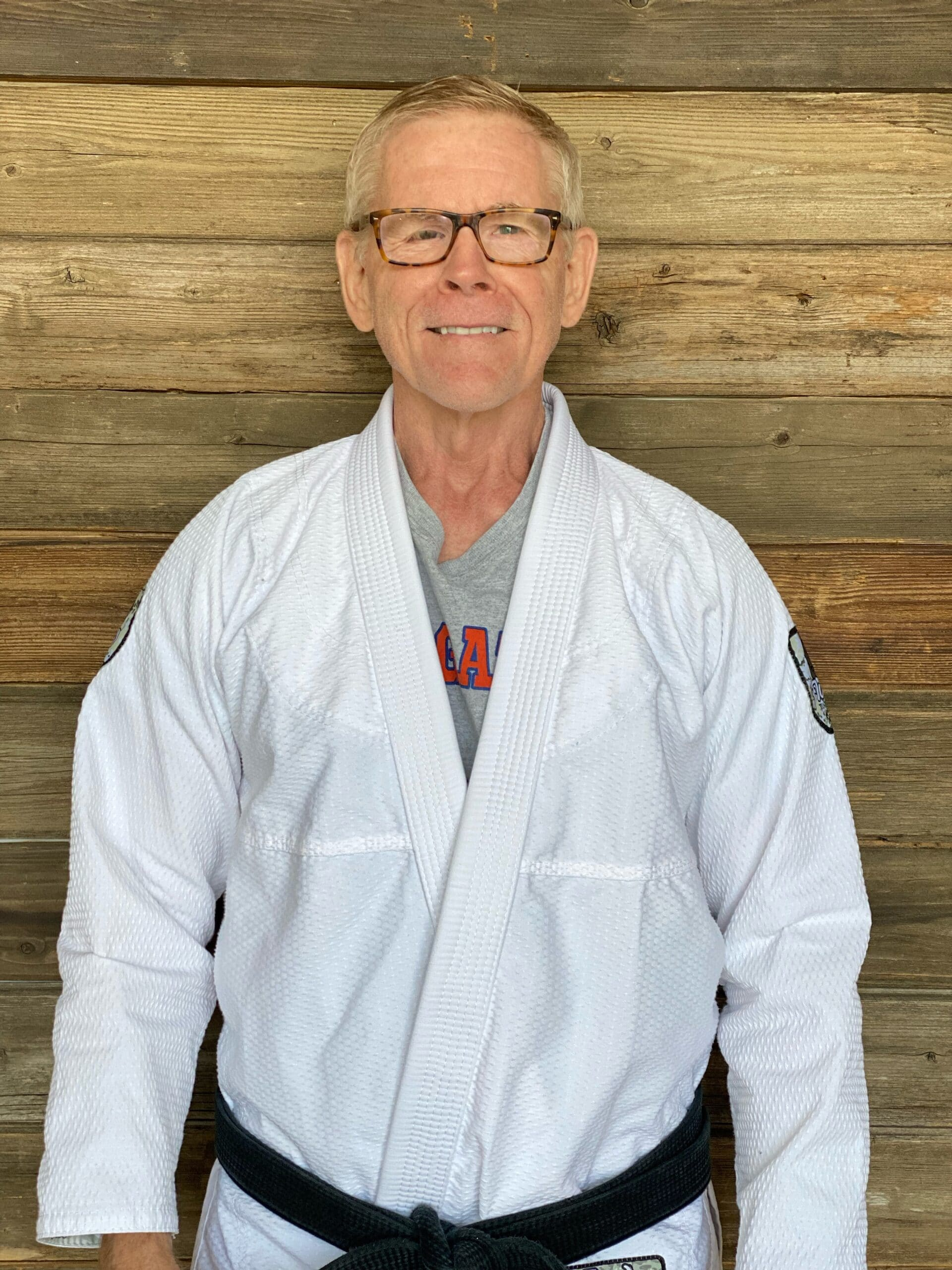 Professor Doug Fornberg posing for a picture in a white Jiu-Jitsu gi with his black belt on in Blaine MN