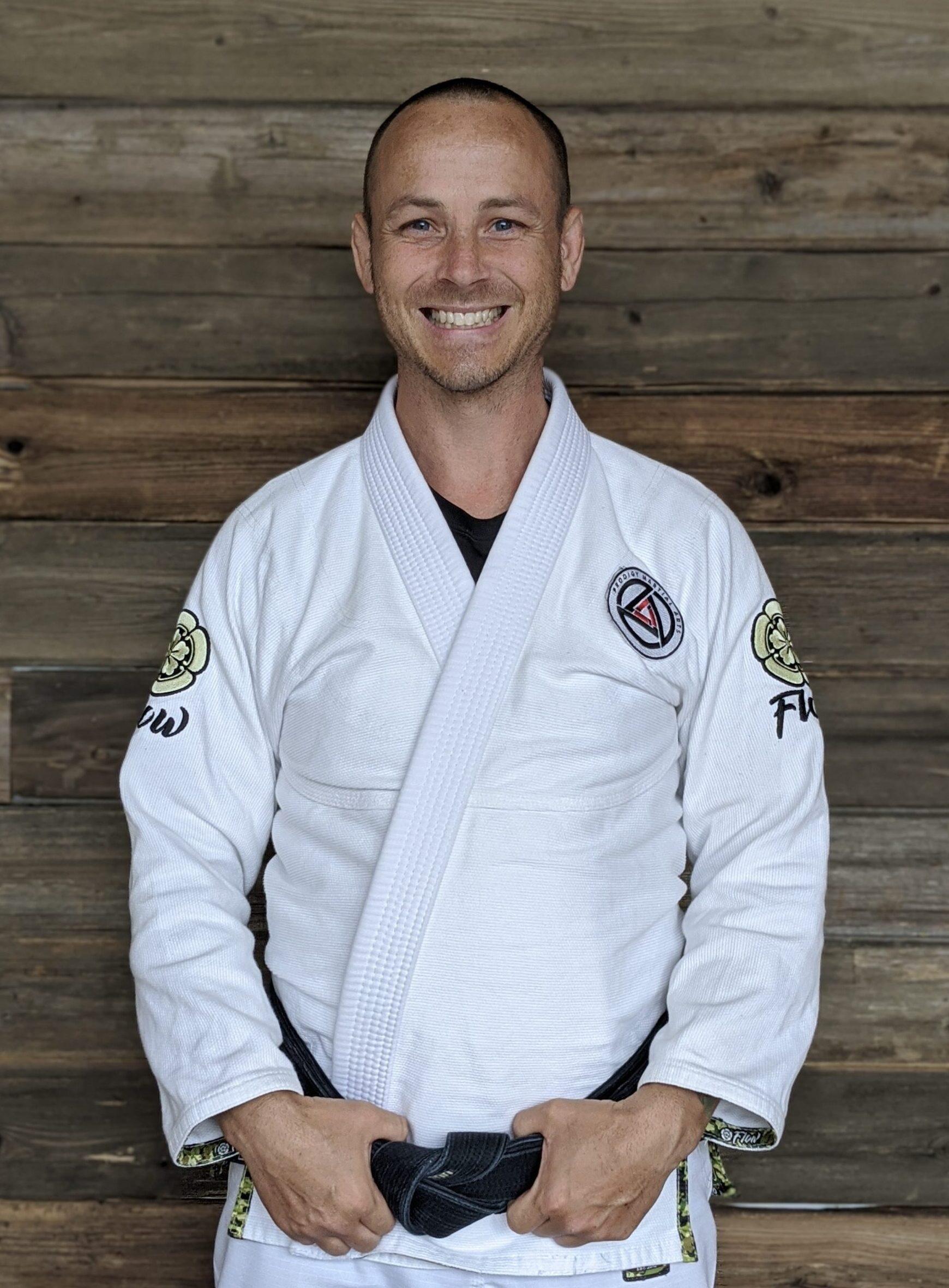 Professor Justin Kahmann posing for a picture in a white Jiu-Jitsu gi with his black belt on in Blaine MN