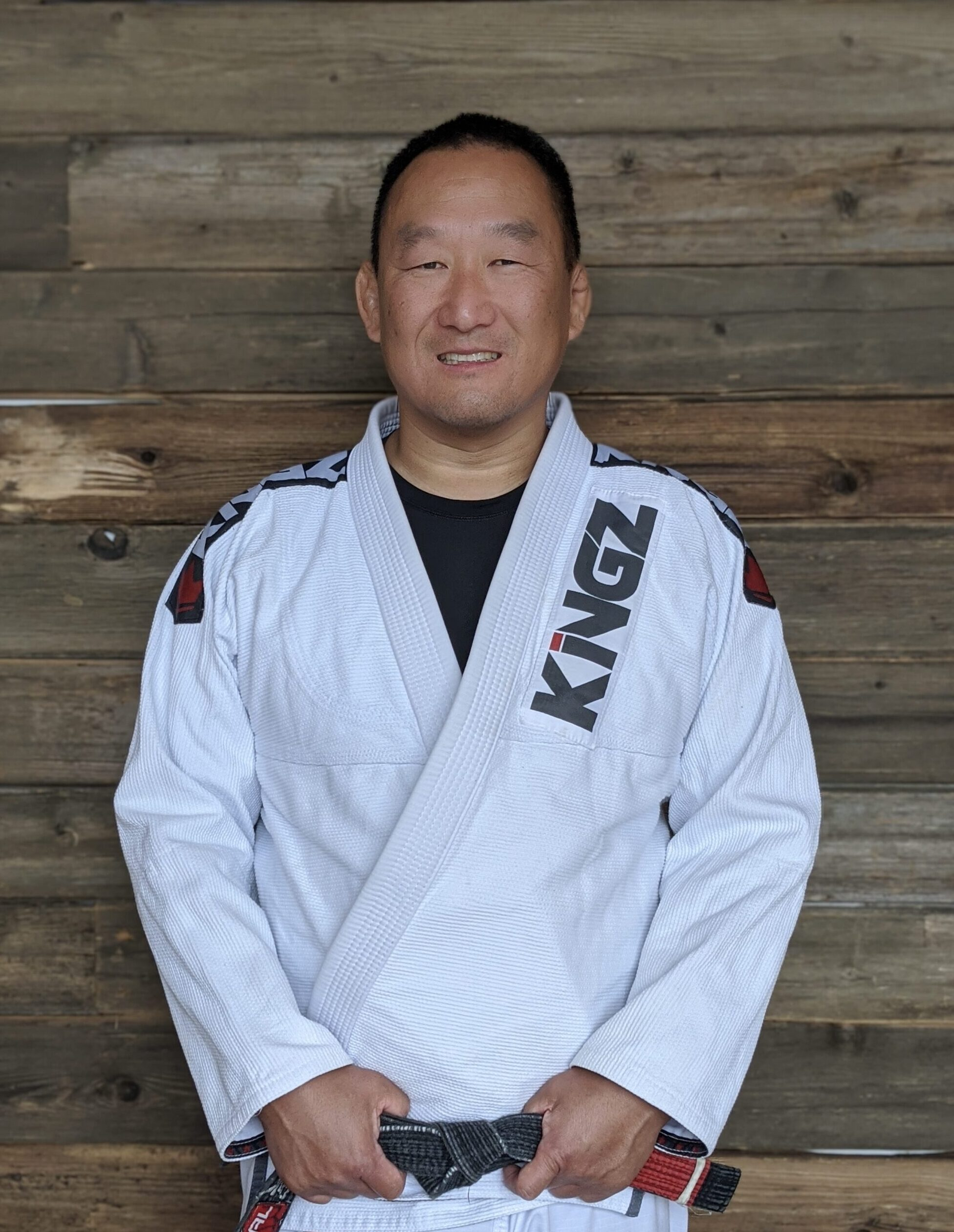 Professor Mike posing for a picture in a white Jiu-Jitsu gi with his black belt on in Blaine MN