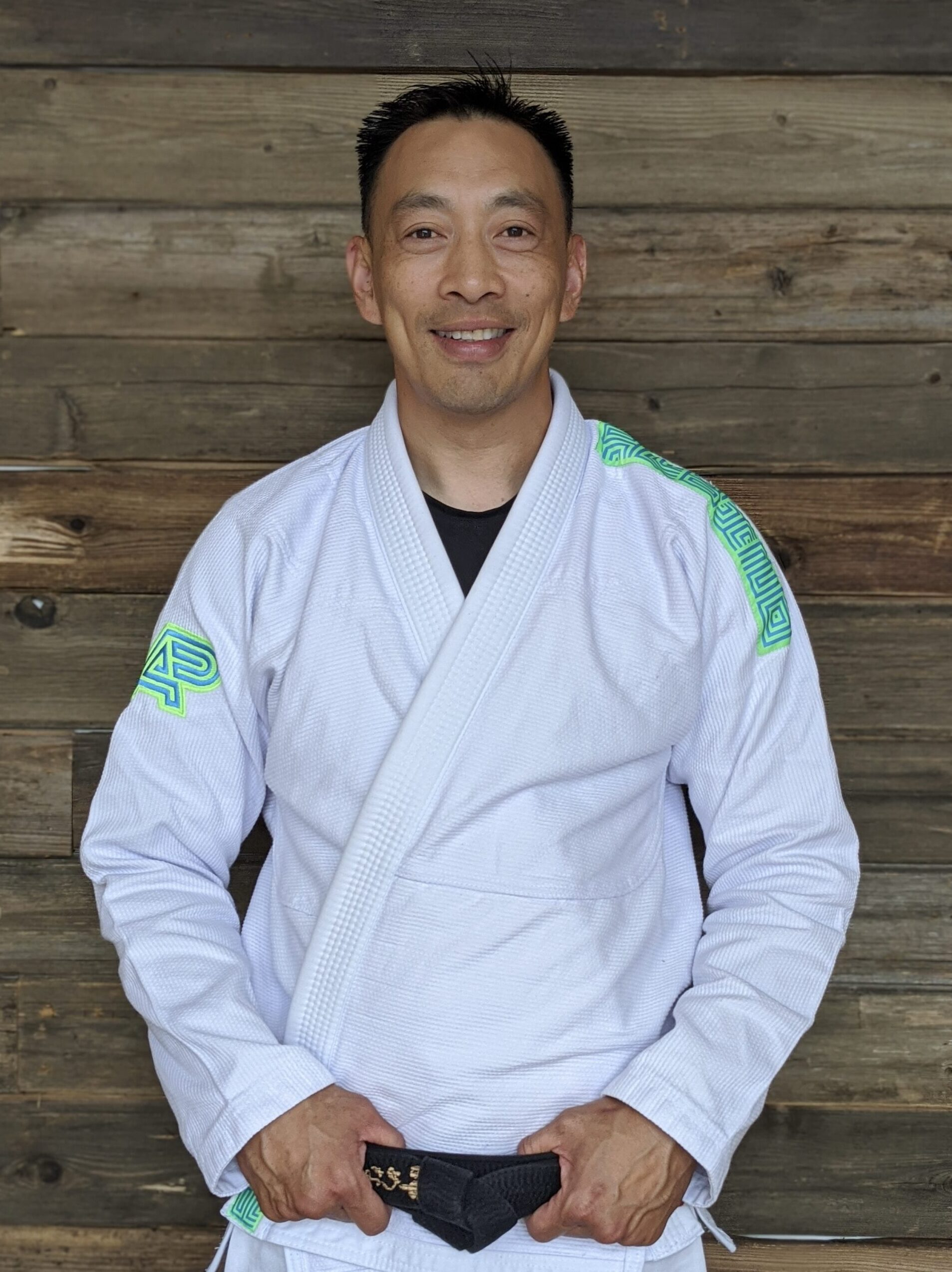 Professor Thao Le posing for a picture in a white Jiu-Jitsu gi with his black belt on in Blaine MN