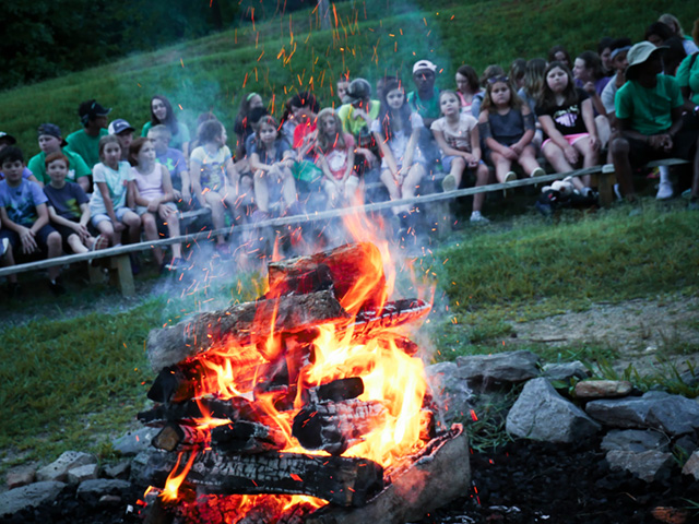 Campfire area with seating and a stage. This area is right in front of the lake.