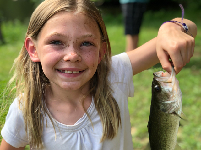 Great fishing opportunities in the lake. This child is holding up her catch.