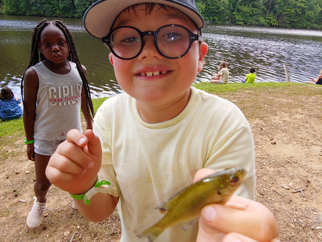A boy holding a small fish.