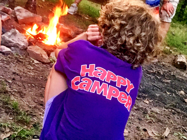 child sitting at the campfire with a happy camper shirt on.